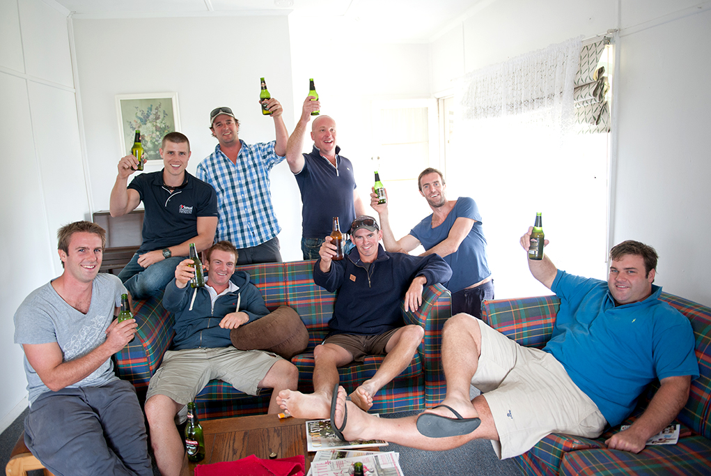 groom, casual, relaxing, beer, groomsmen, chilling, couches, cheers, thongs, jumpers, newspaper, wooden coffee table, happy, wedding, day, photographer, rural, country, family home, South Australia, photography