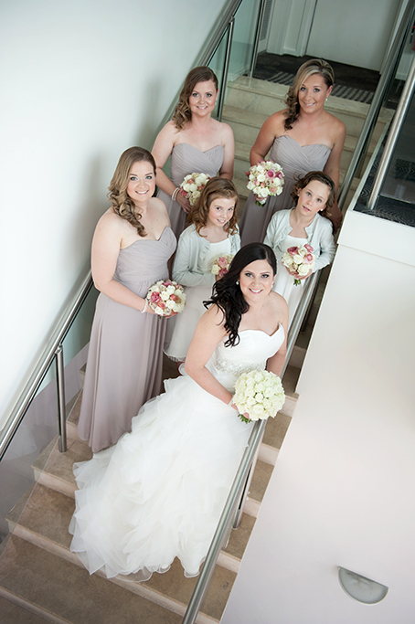 happy bride bridesmaids Adelaide photographer flower-girl white wedding dress roses bouquet pink grey silver strapless Sferas Convention Centre staircase accommodation stairs photography