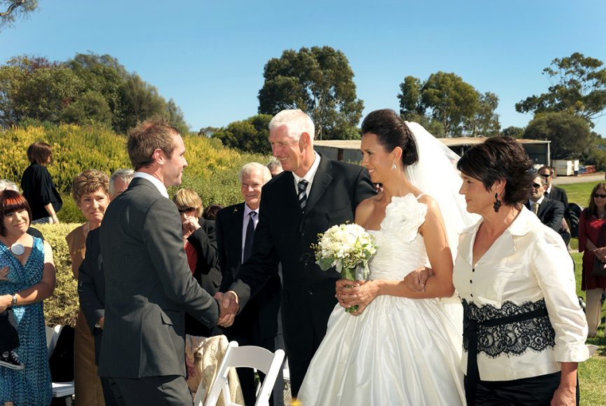 ceremony sunny day wedding guests happy bride parents mum dad groom hand shake Adelaide photographer trees white flowers roses bouquet silver accessories earrings hair up-do South Australia photography