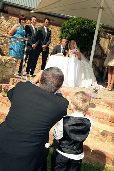 Paige-boy happy photographer couple newlyweds groom bridal party guests wedding Adelaide Paxton Winery signing Marriage Certificate dress feather pen South Australia pink flowers bride photography