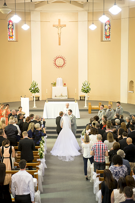 happy church bride groom bridal party bridesmaids groomsmen Italian wedding ceremony Adelaide flowers bouquet dress peach dresses grey suits candles guests photography Adelaide photographer