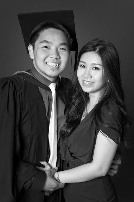 black and white formal studio graduation portrait on mid grey background