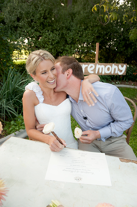 kissing, flower pens, roses, certificate, wedding, ceremony, bride, wood, chair, table, rustic, outback, rural, photography, South Australia, dress, blue shirt, pants, photographer, ring, happy, groom, trees, greenery