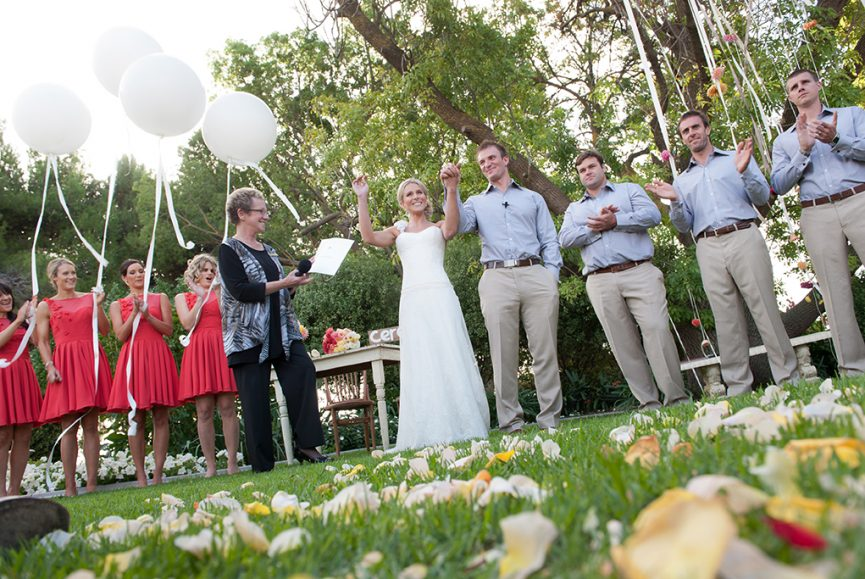 bridal party, groomsmen, groom, bridesmaids, bride, ceremony, outdoors, greenery, white balloons, cherry pink, blue shirt, brown belt, shoes, dress, rural, rose petals, yellow, white, bouquet, flowers, apricot, pink, country, celebrant, happy, photographer, South Australia, trees, wood, chair, photography
