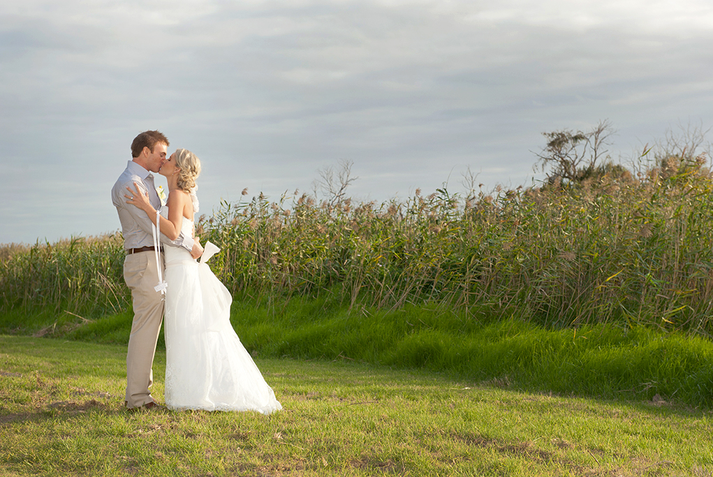 photographer, grey sky, clouds, lake, photography, grass, shrubs, South Australia, rural, outback, country, groom, bride, kiss, dress, blue shirt, pants, brown leather belt, shoes, wedding