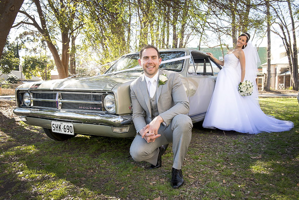 Holden Classic Adelaide parkland trees bride groom wedding dress strapless bouquet white gold silver accessories necklace headband earrings groom grey suit black shoes white rose tie photographer Australia photography