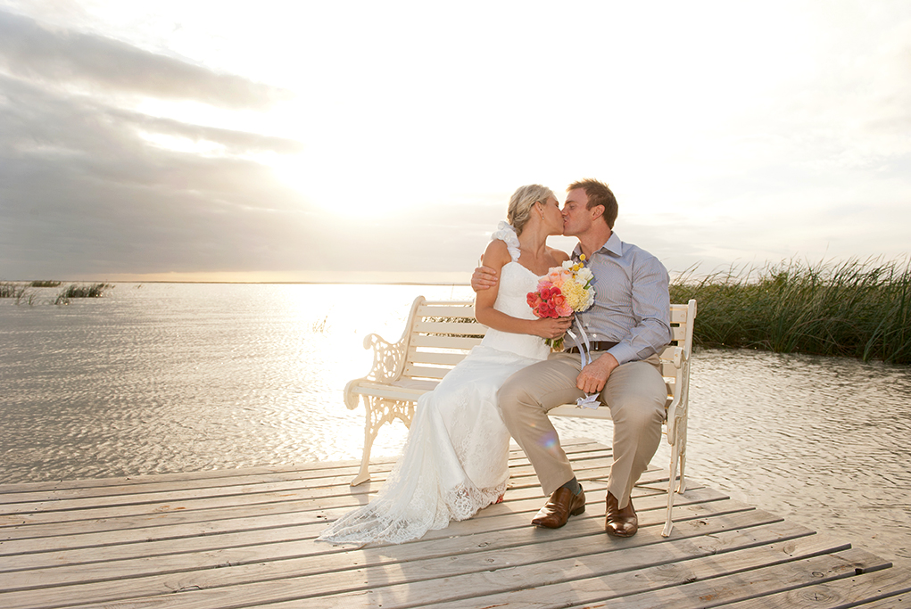 lake, chair, romantic, photography, lakefront, happy, love, kiss, bride, groom, evening, sun, sunset, photographer, South Australia, dress, flowers, colorful, bouquet, pink, apricot, yellow, white, blue shirt, wood, leather, brown, shoes, belt, rural, country, outback