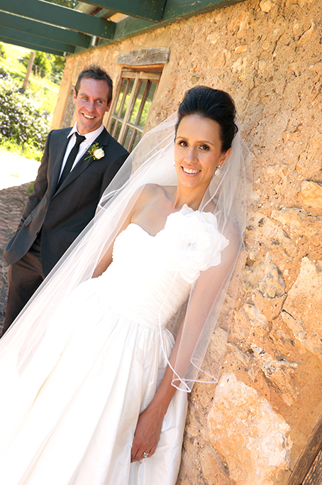 Dress wedding white flower hair up-do bride grey suit photographer groom veil winery Adelaide rose happy couple newlyweds photography South Australia