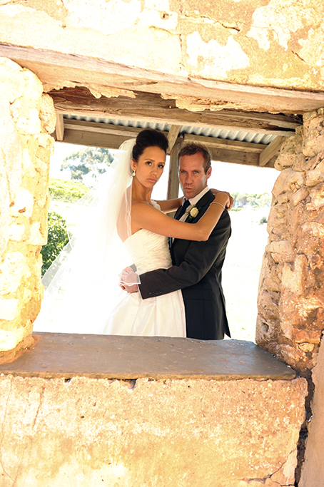 pout brick wall happy fun pouting couple pose wedding photography Adelaide white rose dress veil grey suit South Australia hair up-do silver accessories photographer