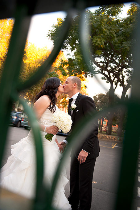 kiss bride groom kissing Adelaide happy couple newlyweds South Australia fence photography white wedding dress roses bouquet black suit tie silver accessories love
