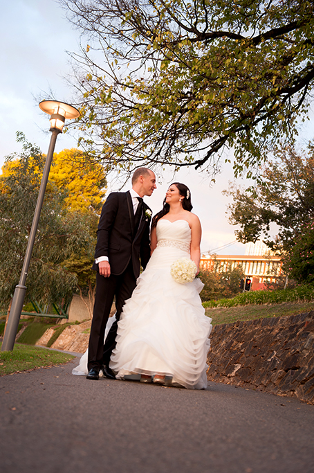 happy newlyweds couple walking wedding dress Adelaide river park Torrens love white roses flowers bouquet black suit tie photography South Australia Photographer nature trees