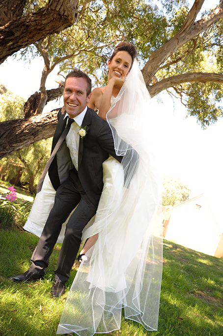 bride groom piggy-back happy veil fun photography Adelaide trees pink flowers white rose grey suit shoes dress South Australia photographer wedding