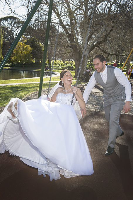 Adelaide parkland Australia fun happy bride groom playground swings trees grey suit vest white tie dress strapless sequins accessories silver white gold headband photography necklace earrings heels shoes photographer