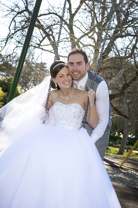 playground park Adelaide swings love newlyweds groom bride grey suit wedding dress strapless trees sequins necklace silver accessories photography earrings white gold headband photographer