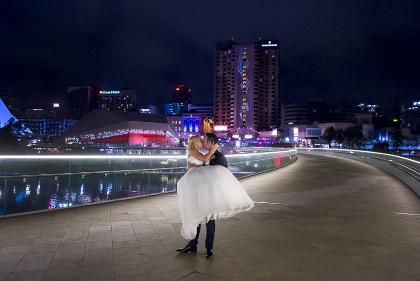 happy, romantic, newlyweds, love, kiss, Adelaide, Italian, couple, wedding, South Australia, casino, footbridge, neon lights, fringe festival, art, Gainsborough Studio, dress, white, silver accessories, blue suit, pink, purple, city-scape,  photographer, photography