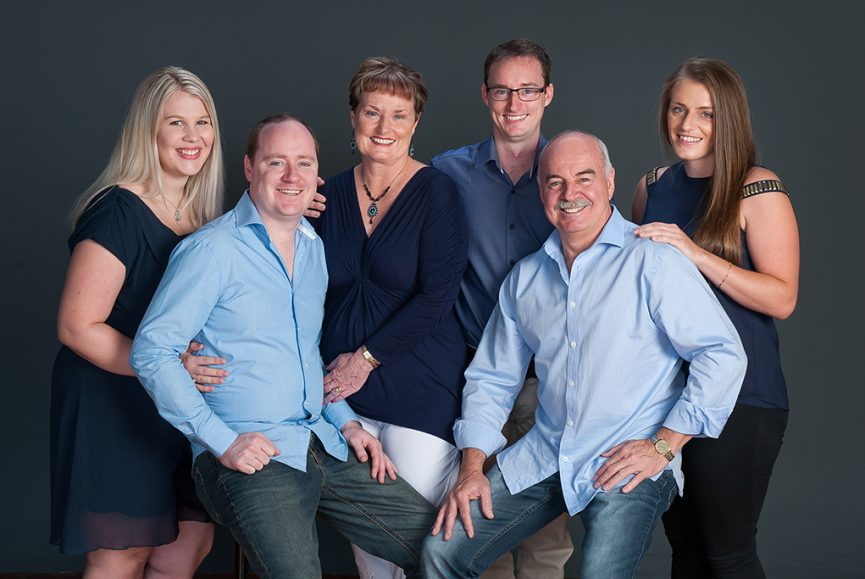 relaxed studio portrait of family of 6 on mid grey background