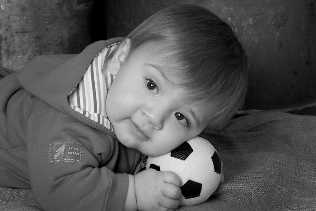 Studio shot of little boy junior soccer player in black and white