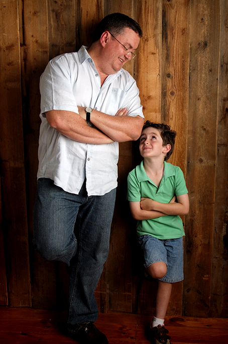 colour dad and son on casual timber background with jeans and casual tops