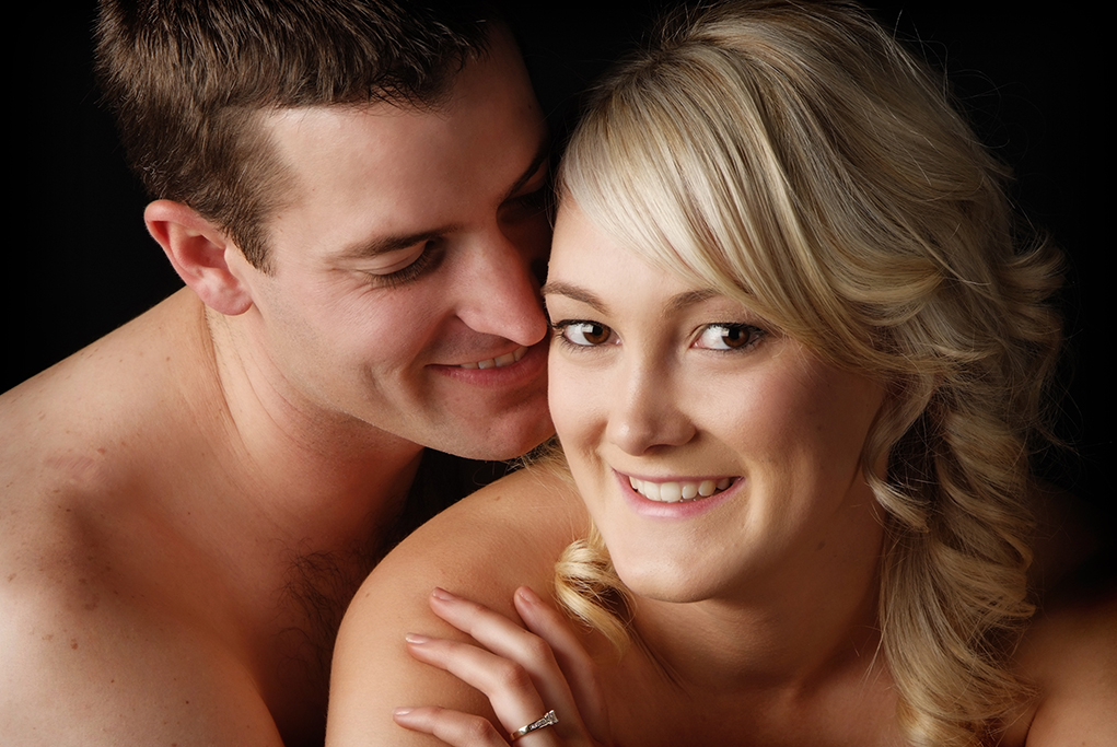 romantic sexy colour studio portrait of young engaged couple with bare skin