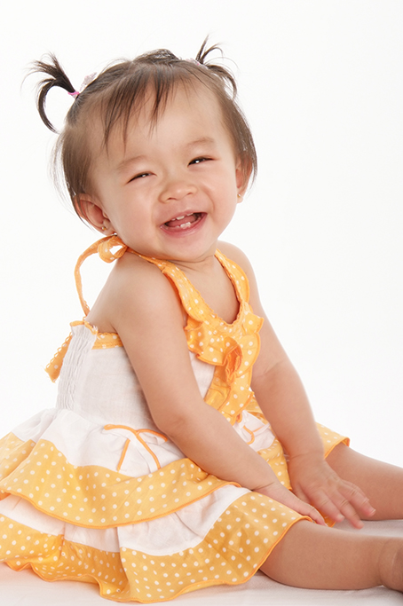 modern studio shot of smiling happy asain little girl smiling laughing wearing soft yellow and white spotted dress with cute pigtails