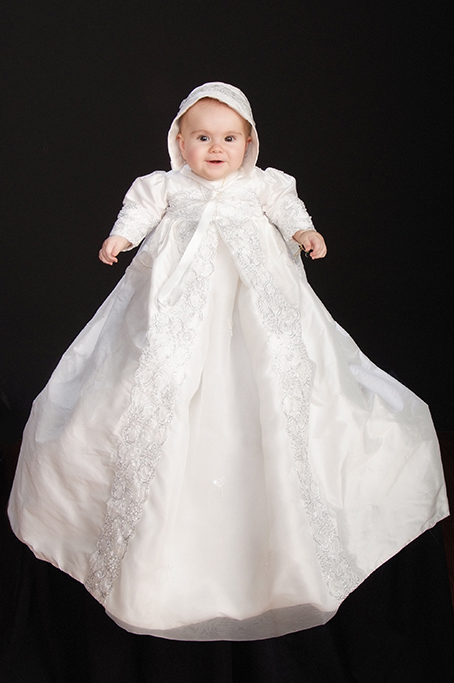 Formal studio portrait of babys christening showing full length christening gown with seed pearls bow and bonnett on a black background