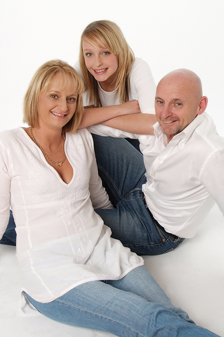 modern family on white background wearing denim jeans and white shirts