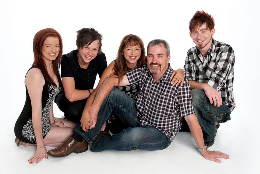 colour relaxed family portrait of family of 5 with casual clothing jeans and shirts on a white background