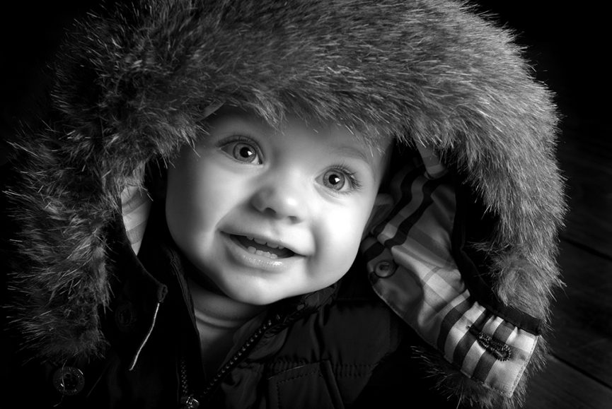 black and white picture of smiling happy baby boy photographed in the studio wearing dark jacket with furry ski hoddie