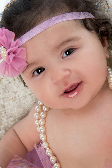 beautiful colour studio portrait of baby girl with pink flower headband and white pearl necklace