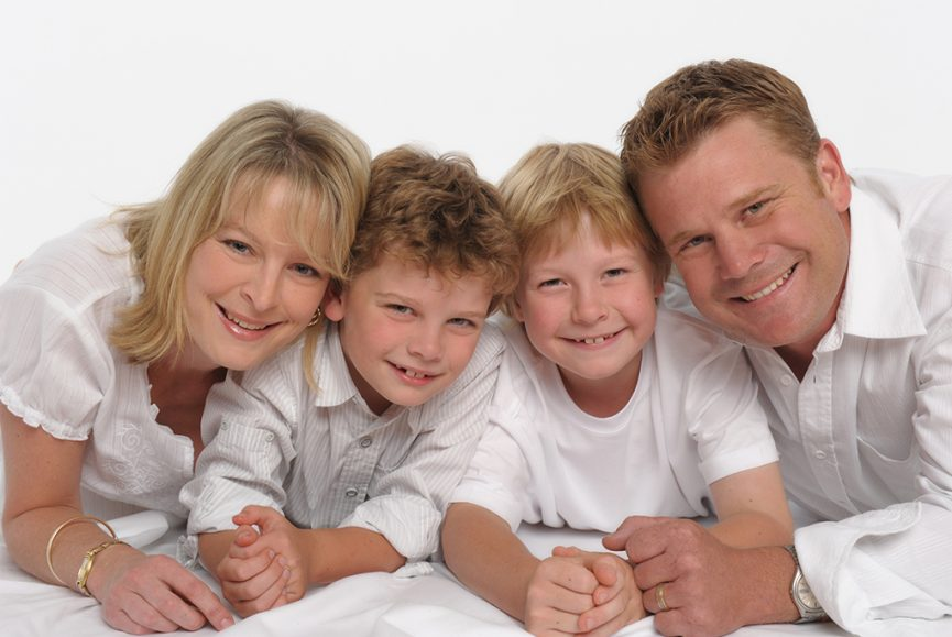 casual family portrait with mum dad and 2 young sons wearing casual white tops shot on white background