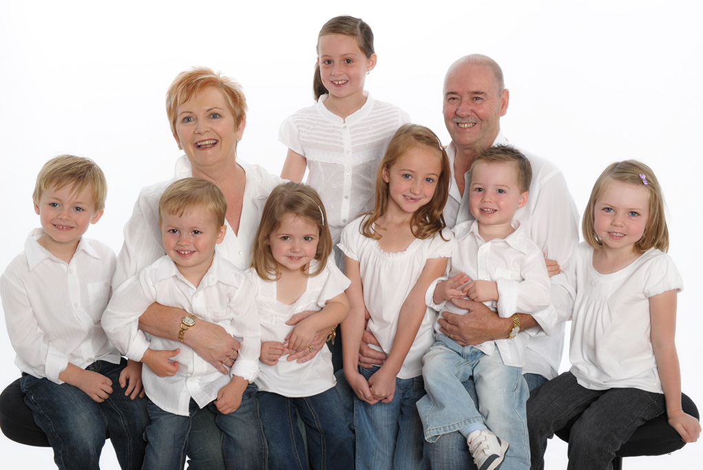 grandparents and 7 grandchildren on white modern background dressed in denim jeans and casual white tops