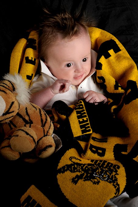 colour studio photograph of cute baby boy tigers football fan draped in his dads tigers football scarfe with toy tiger