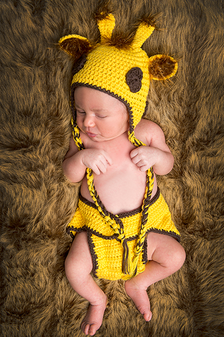 Colour studio full lenght portrait of adorable sleeping baby boy in knitted giraffe outfit and laying on fluffy brown rug