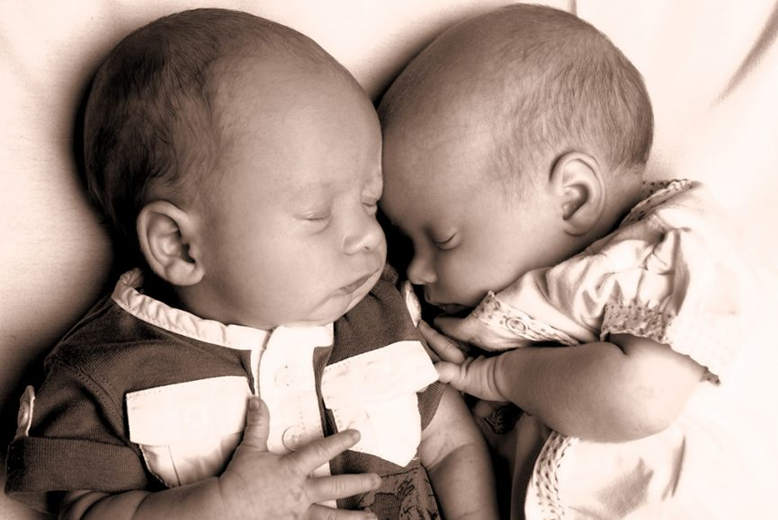 Adorable sepia studio portrait of two sleeping twins with cute chubby fingers