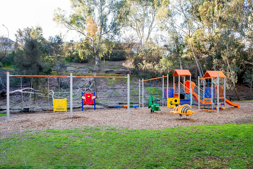 Brightly coloured, red, green, orange. yellow, blue and black Playground equipment photograph located in a grassy area in Tea Tree Gully South Australia near the River Torrens