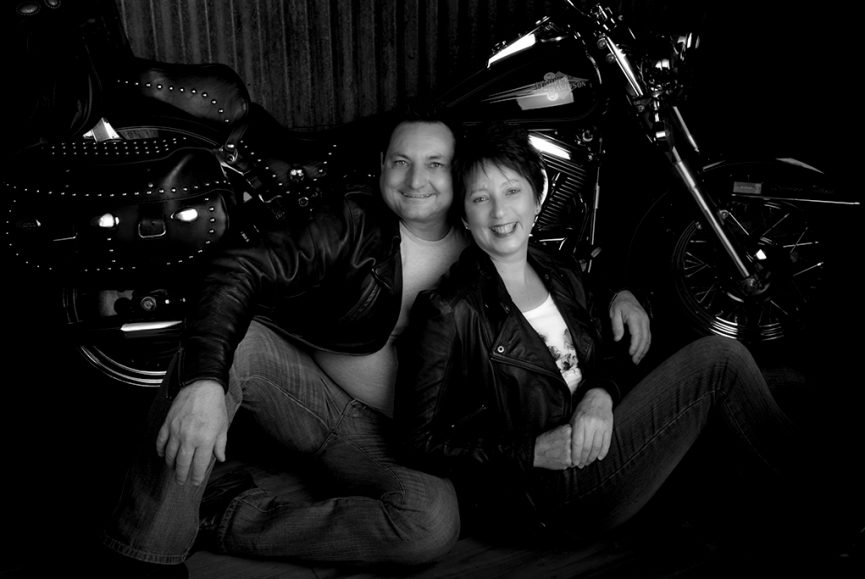 black and white studio portrait of a couple with a harley davidson heritage softail motorbike