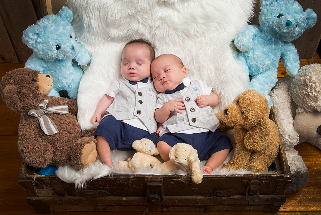 colour studio portrait of Twin baby boys in vinatge style sleeping on white fluffy rug in old suitcase surrounded by to teddy bears