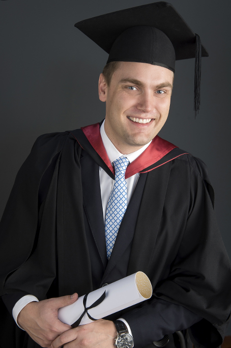 formal graduation portrait with formal robes and grey background