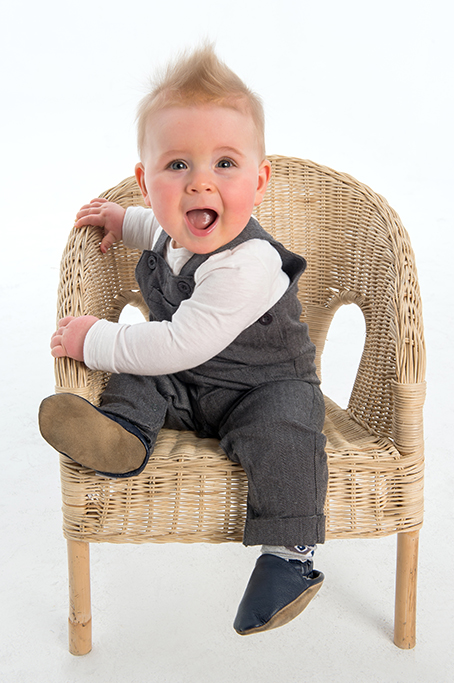 moderb fun colour studio portrait of little boy in grey suit outfit sitting on small cane chair photographed on a whote background