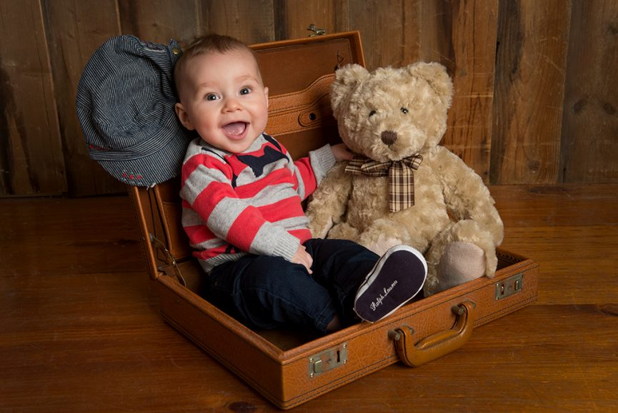 vintage looking colour studio portrait of baby boy sitting in old fashioned briefcase with his favourite brown teddy bear