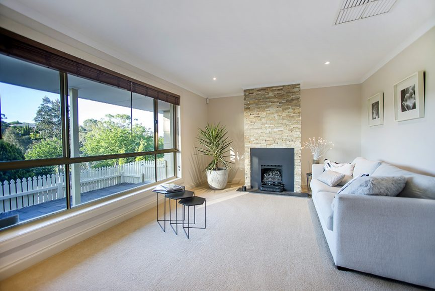 House and realestate photography, image of lounge room taken late afternoon in Golden Grove, modern setting, luxe, stone fireplace