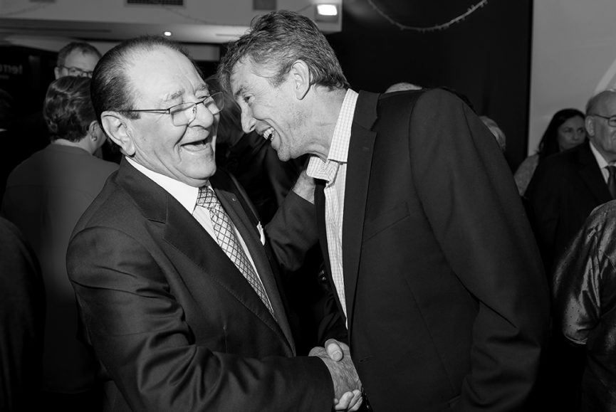Corporate meet and greet, fun moment showing black and white image of two business men shaking hands at a corporate event launch for Karidis Corp