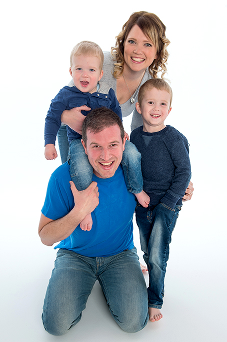 fun colour cassual modern family portrait of mum dad and 2 young sons wearing denim jeans and casual jumpers and tshirts