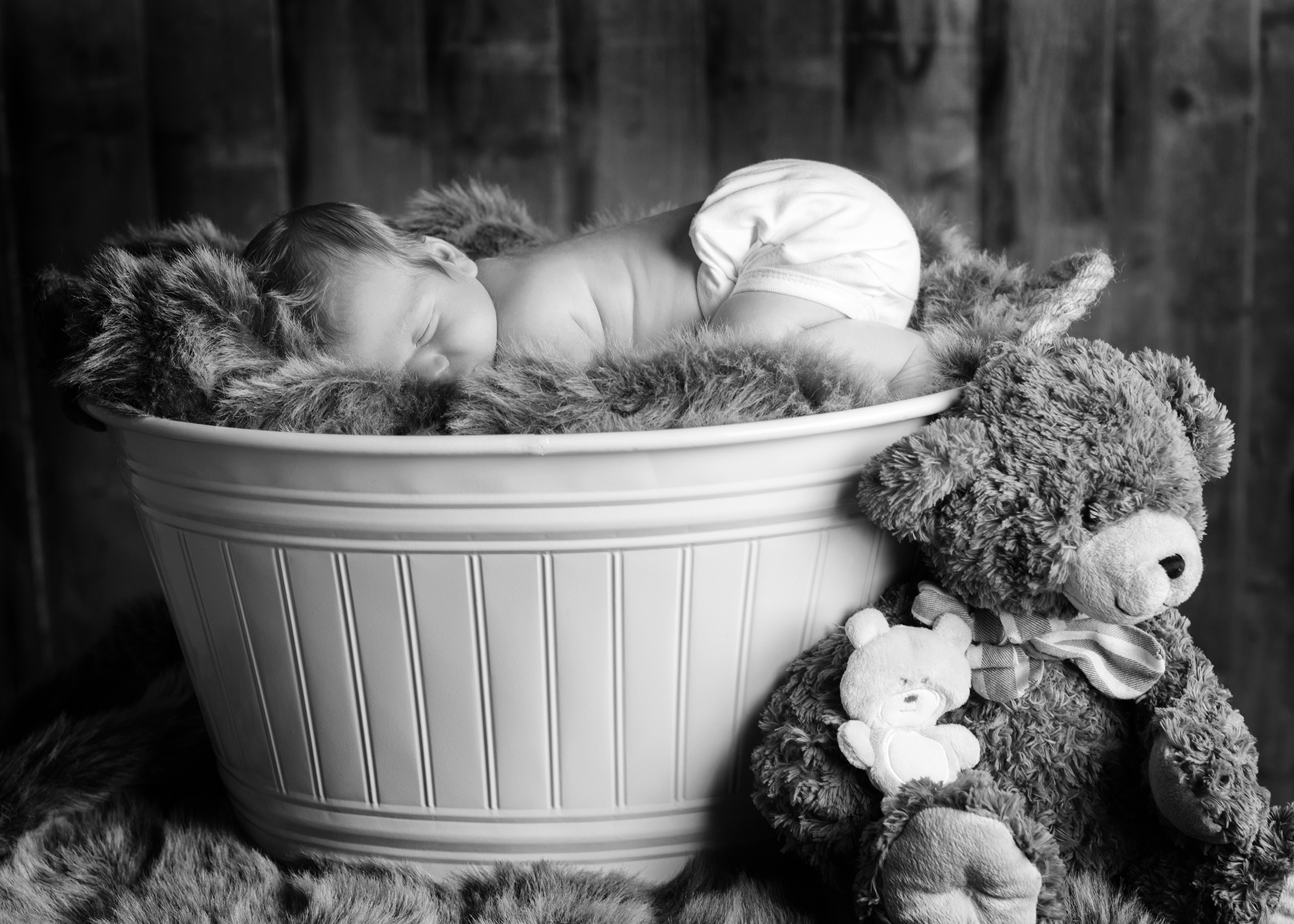 black and white studio shot of baby sleeping on top of fluffy rug in old vintage white metal wash tub with teddy bear