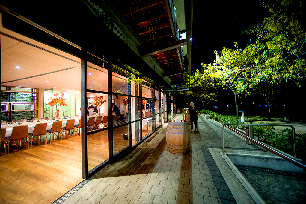 Corporate event photograph featuring the Vines room at the National Wine Centre, wine makers diner, evening nighttime photography, exterior building shot of the National Wine Centre at Night showing warm timber floors and themed event decor