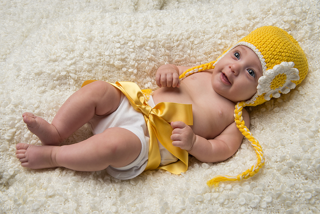 White and yellow fun and happy theme modern colour studio shot of baby with yellow knitted bonnett and yellow ribbon around its waist laying on white fluffy rug