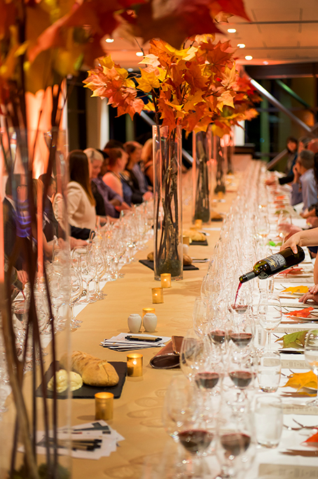 Corporate event image, wine makers dinner, themed event photograph featuring tall  glass vases filled with flowers, crystal glassware and waiter pouring red wine