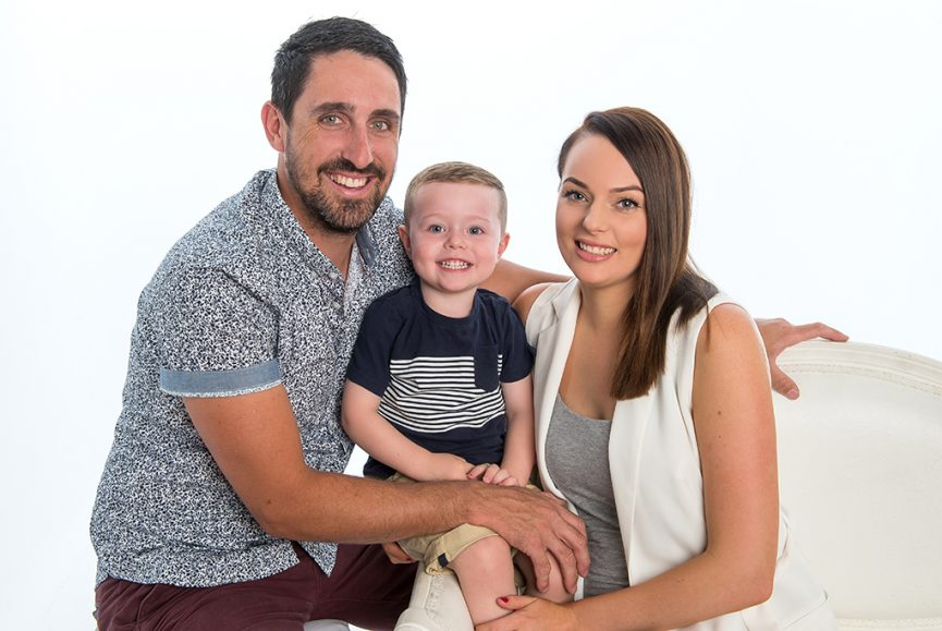 relaxed casual portrait of mum dad and baby son on white background
