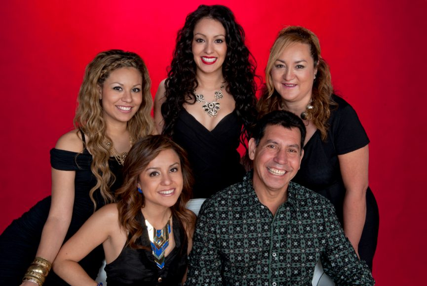 modern relaxed colour family portrait of spanish family wearing black tops on red background