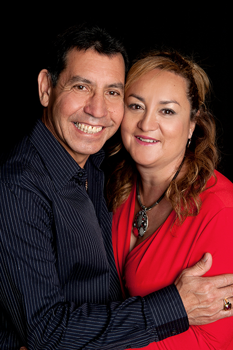 formal studio portrait session of couple wearing black and red shirts on a black background